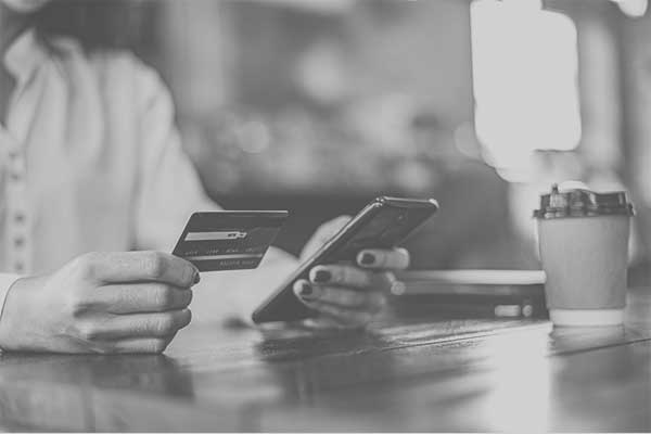 mulher segurando um celular e um cartão de crédito sentada em uma cafeteria